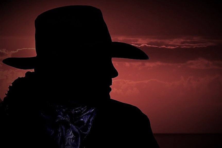 Cowboy silhouette against a red sky